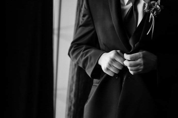 A close up black and white wedding photo of a groom buttoning his jacket