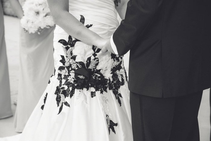 A close up black and white wedding shot of a couple holding hands