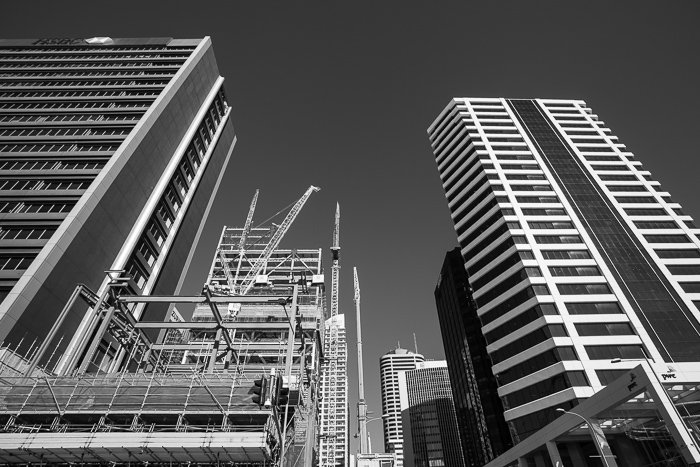 A black and white street photography shot of downtown Auckland, New Zealand on a bright sunny day.