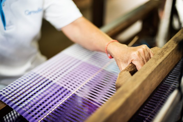 Close up shots of a Thai woman working on a traditional loom weaving silk.