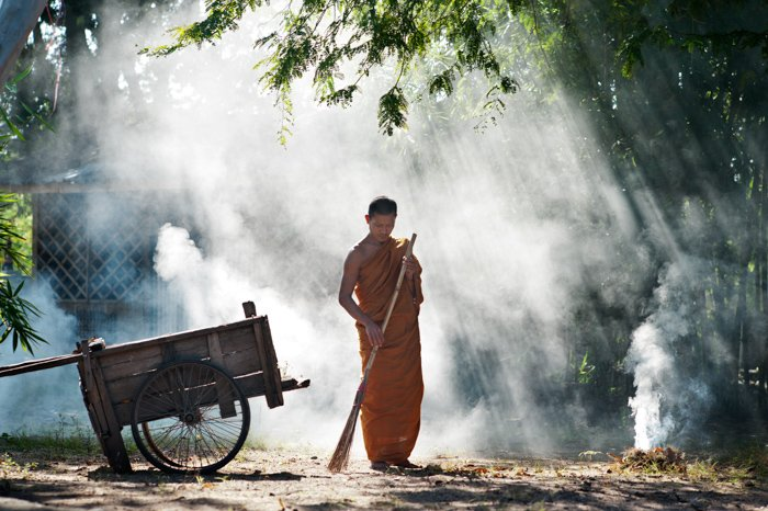 A Buddhist monk sweeps the temple grounds. Editorial photography.