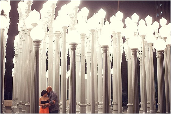 A romantic engagement photography shot of a couple in front of columns of white lamp sculptures