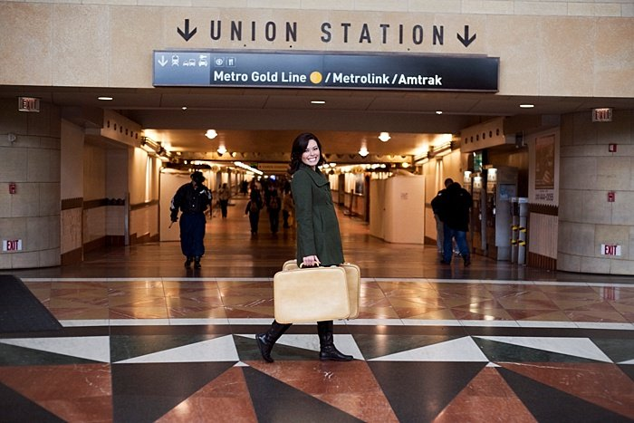 An environmental portrait of a girl with suitcases posing at union station