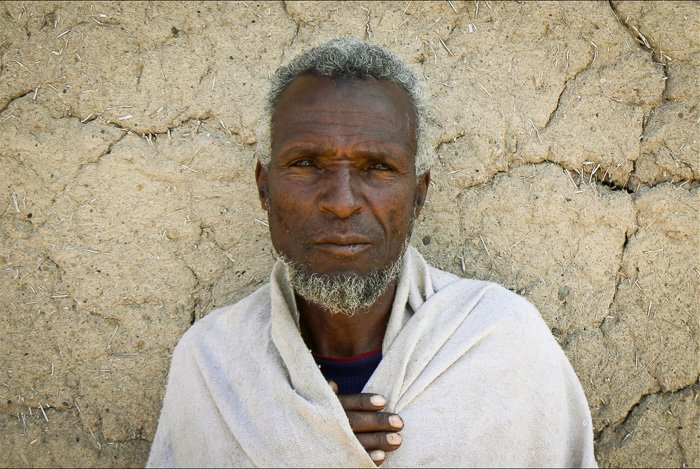Portrait of an old man in front of a wall - find a fixer for better travel photography
