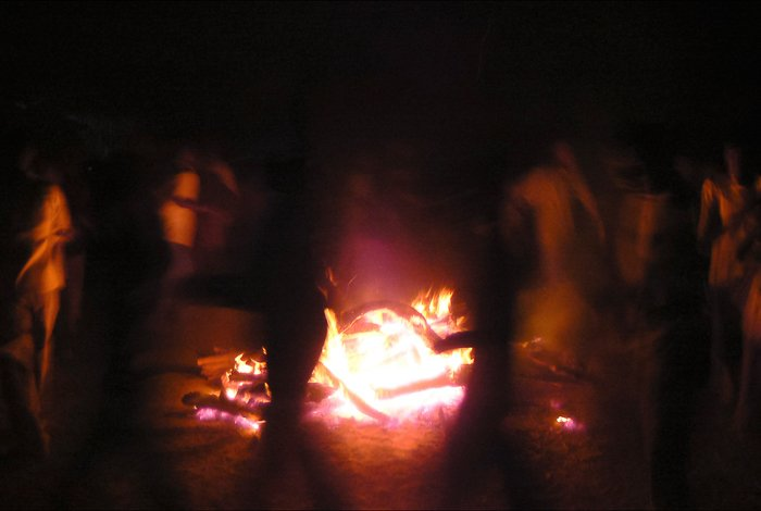 Atmospheric travel photography shot of people dancing around a fire