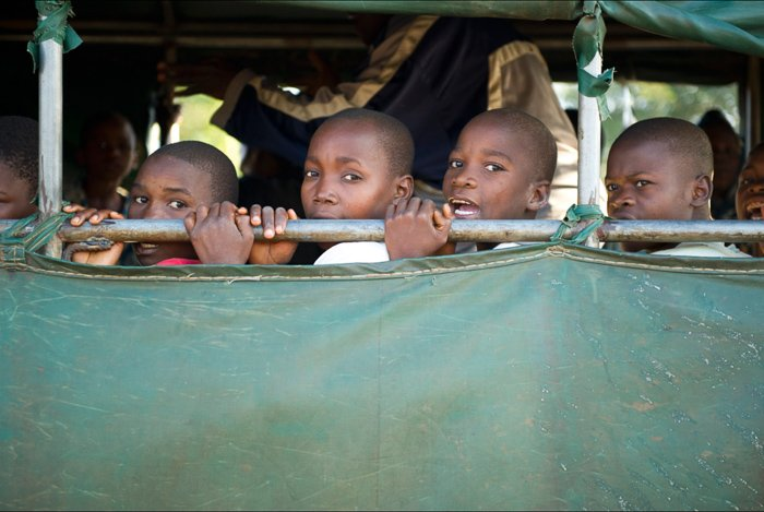 Portrait of a group of young boys behind green tarpaulin - local guide for better travel photography