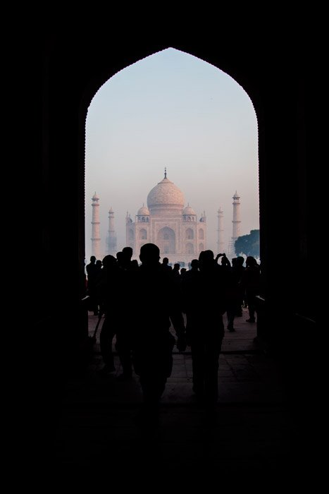 Photo of the silhouettes of people walking through an archway which is naturally framing the photo.
