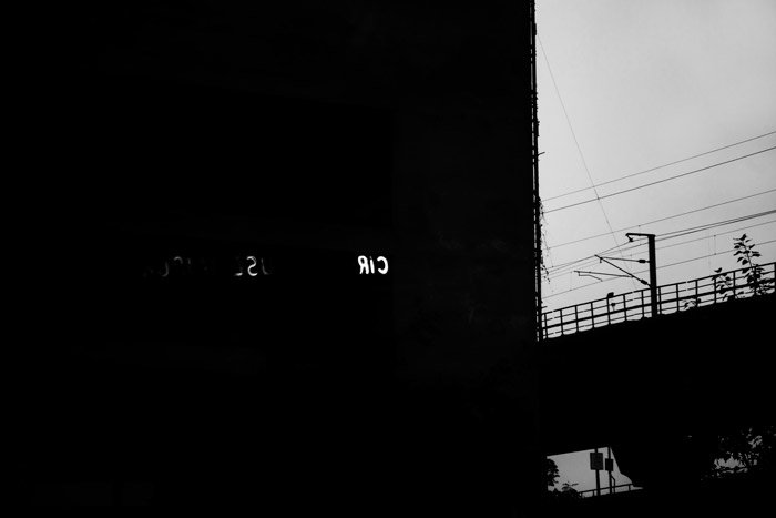 Black and white photograph of silhouettes of buildings. Naturally framing photography.