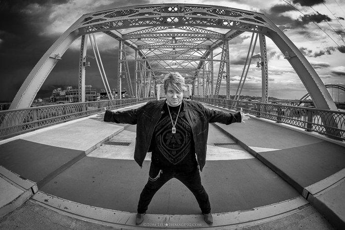A black and white freelance photography portrait of musician Mickey Joe on a bridge