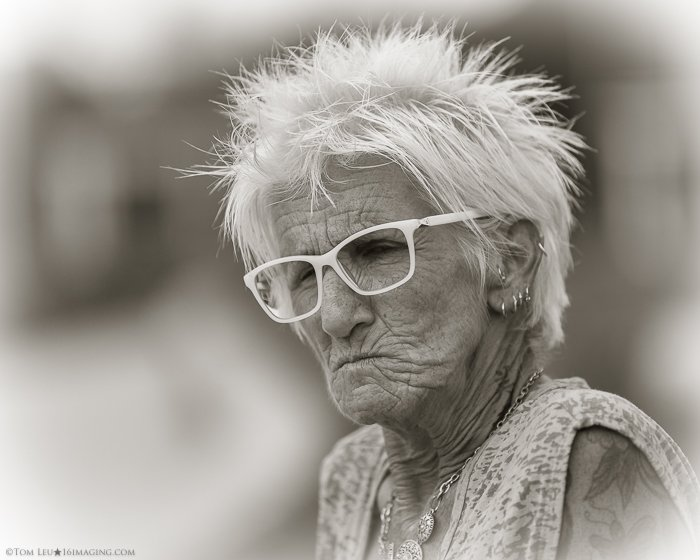 A black and white portrait of an elderly woman in glasses - freelance photography tips