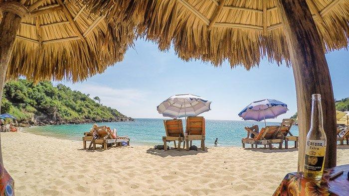 A pretty beach scene framed by straw umbrellas - travel photography jobs