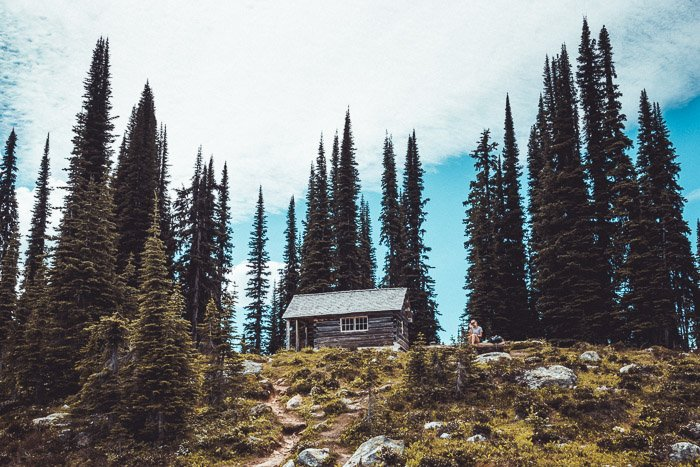 A bright photo of cabin on a hill surrounded by tall trees - how to make money with travel photography