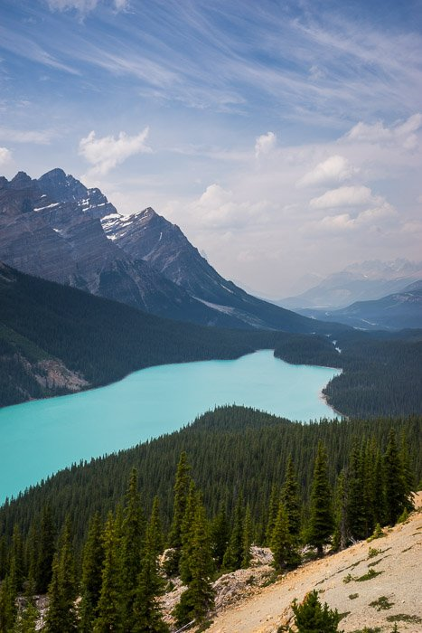 A stunning scenic shot of a blue lake surrounded by forest- make money with travel photography