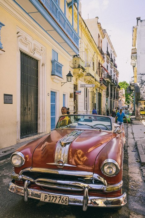 A red car parked on a street in Cuba - how to make money with photography