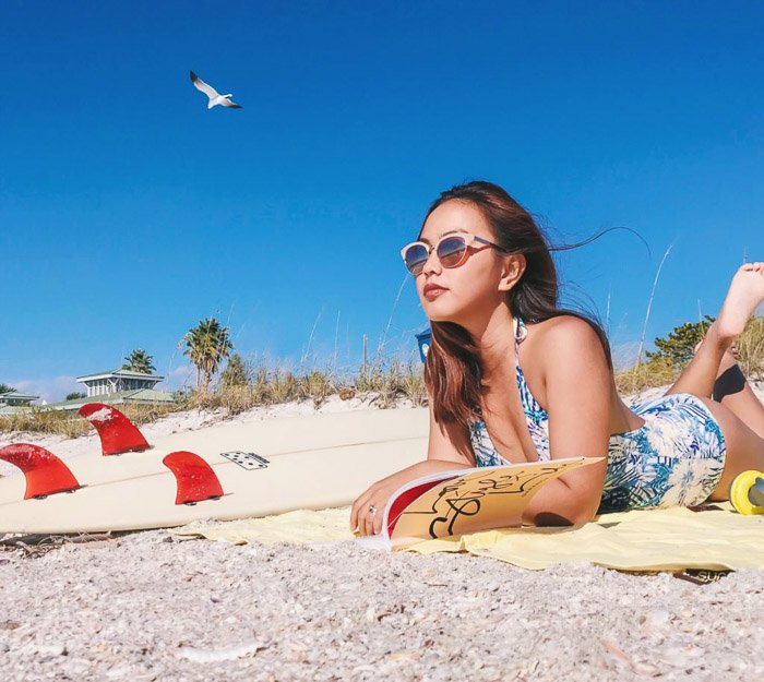 Portrait photography of a girl relaxing on a beach. Instagram tips for social media photography.