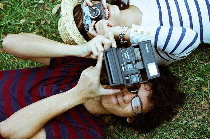 Overhead shot of two people lying on grass, aiming cameras at the photographer. Instagram tips for photography beginners.