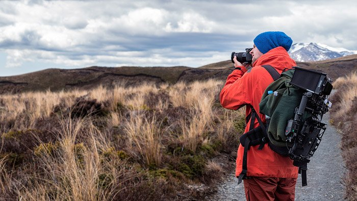 A photographer in red jacket shooting landscape photography