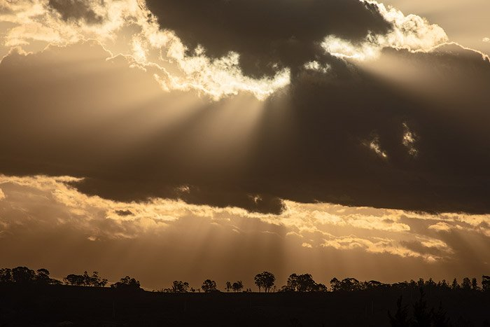 Dramatic clouds over the silhouette of a tree covered landscape