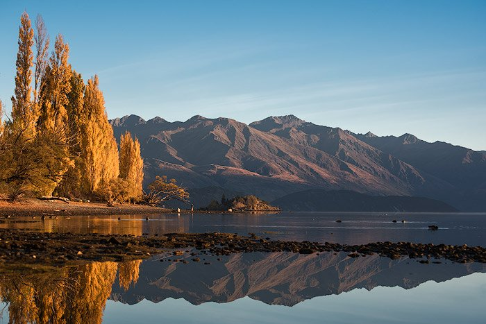 A serene landscape image of mountains and water
