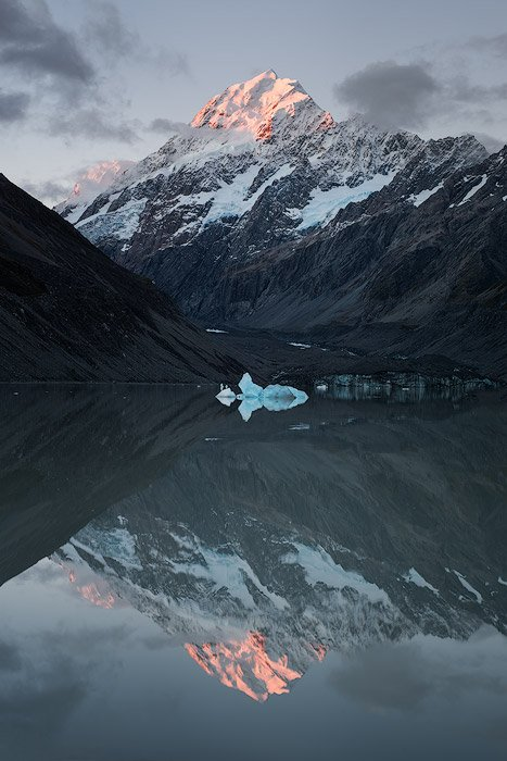 A majestic and dark mountainous landscape mirrored in the water below