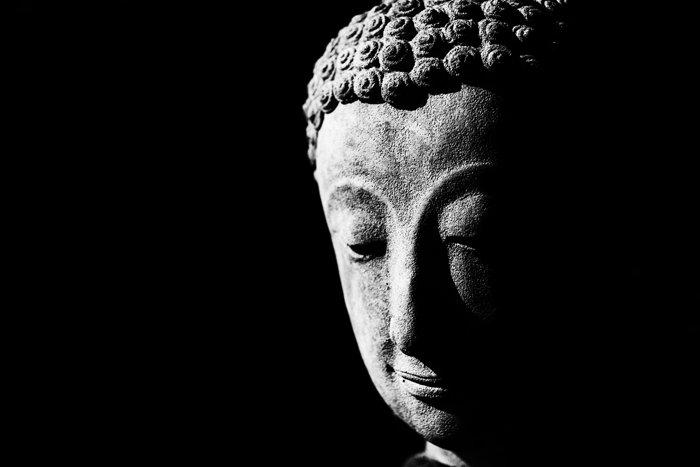 A low key monochrome photography portrait of a statue of buddha.