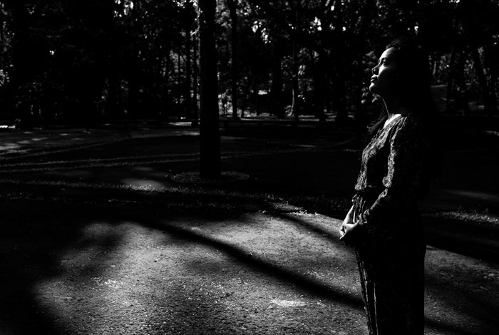 A low key monochrome photography portrait of a girl standing in a dark forest.