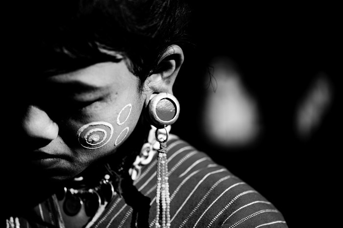 A low key monochrome photography portrait of a person wearing tribal make up and jewelry