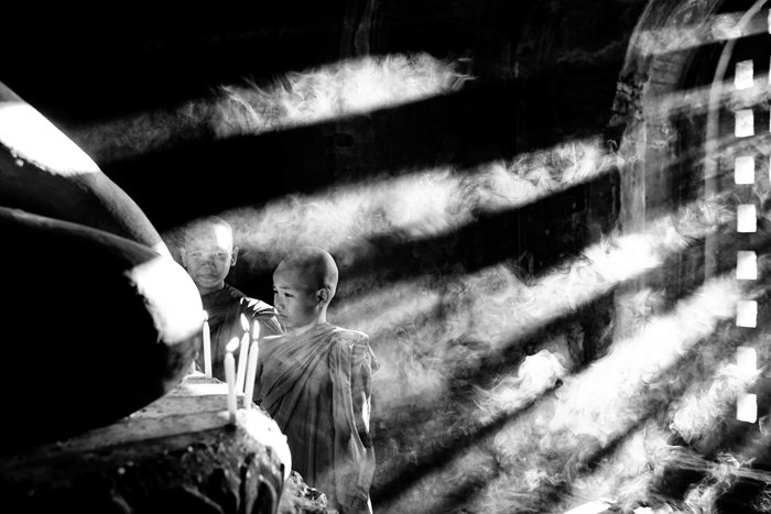 A low key monochrome photography shot of young Buddhists in a temple