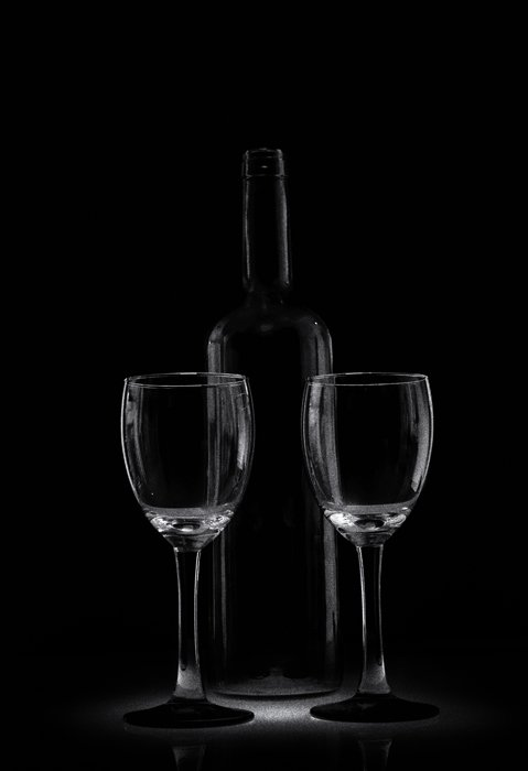 A low key monochrome photography portrait of a wine bottle and two wine glasses