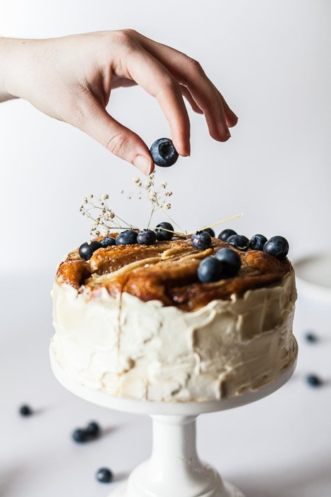 Scrumptious looking food photography shot of hand placing a blueberry on top of a cake against a white background, shot with a macro lens for still life photography