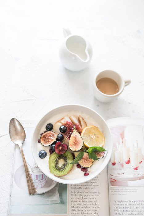 Bright and airy food photography overhead shot of a plate filled with fruit and cream with a spoon, magazine, coffee cup and milk jug shot with a macro lens