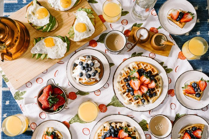 Scrumptious looking food photography overhead shot of a setup of many plates filled with fruit, pastries and eggs on a patterned tablecloth shot with a macro lens