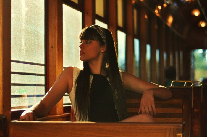 A female poses on a bench looking out the window for fashion model photography shoot.