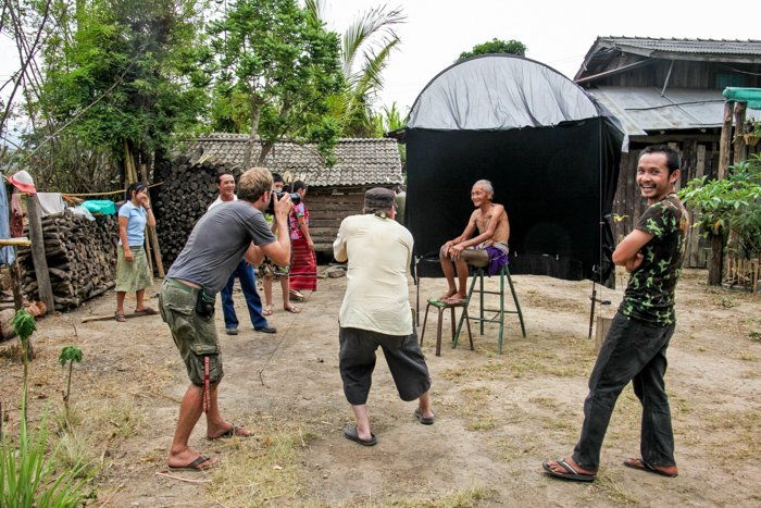A Karen man posing in an outdoor portrait photography studio for photographers and onlookers.