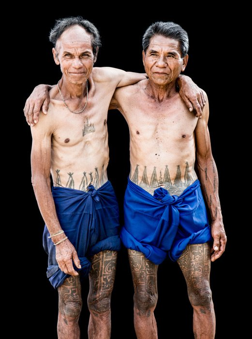 An outdoor portrait photography studio shot of two Karen men with their traditional tattoos.