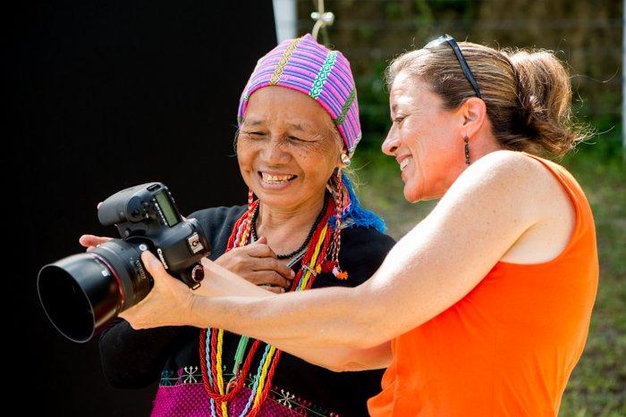 A participant in an outdoor portrait photography studio workshop showing a Karen woman her portrait