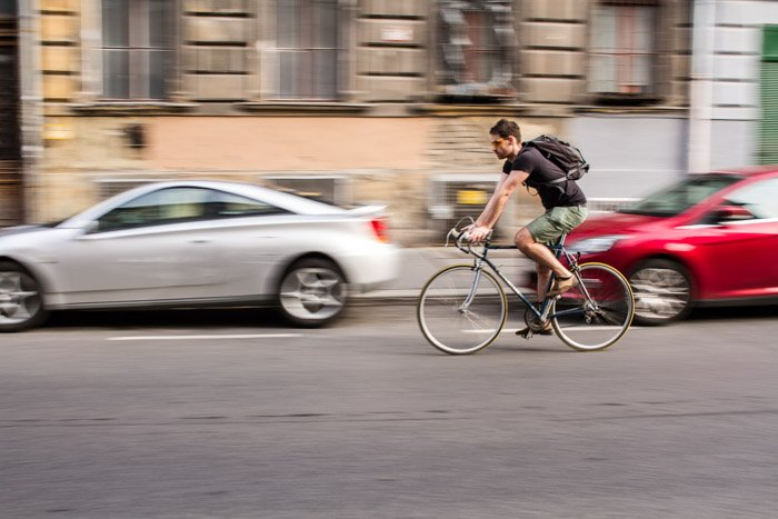 A cyclist on the street with motion blur in the background
