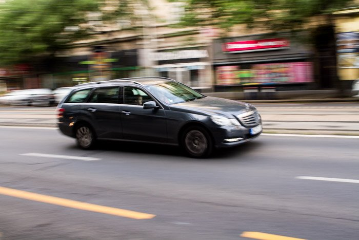 A blurry shot of a grey car driving on the street