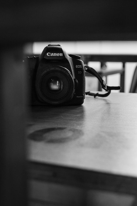 Black and white photography of a canon dslr on a table.