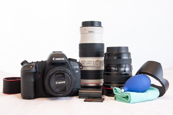 A still life of a canon camera and other photography equipment on a white background.
