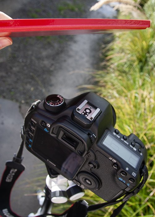 Photo of a tripod and camera with the photographer using a notebook as photography equipment.