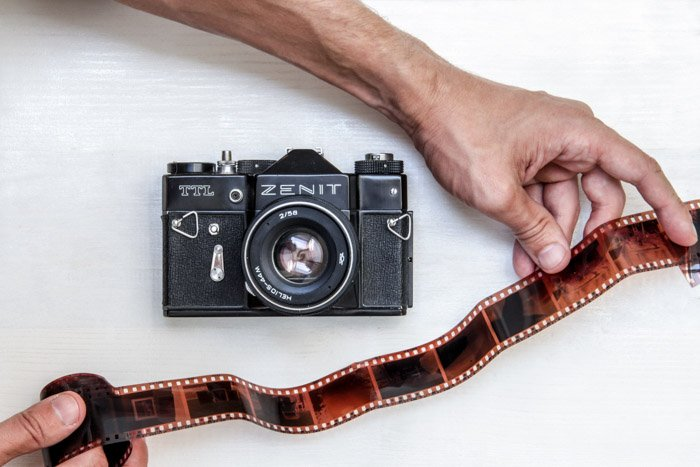 An overhead shot of a zenit camera and a persons hands holding film negatives