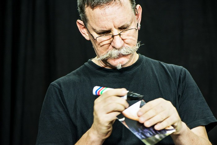 Close up of a man using a black marker to darken the edge of a print for a photomontage.