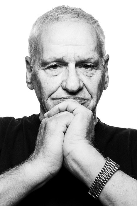 A black and white portrait of a man in the Platon photography style