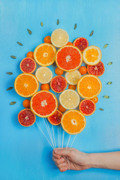 A still life photography ideas arrangement of oranges made to look like a bunch of balloon, on blue background