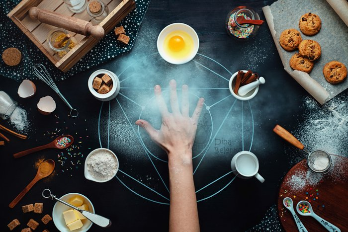 Overhead shot of an outstretched hand in the middle of a fun food photography arrangement on dark background - still life photography ideas.