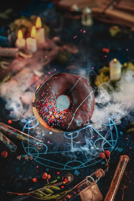Still life photography ideas of flying chocolate glazed donut summoned with an alchemical pentagram