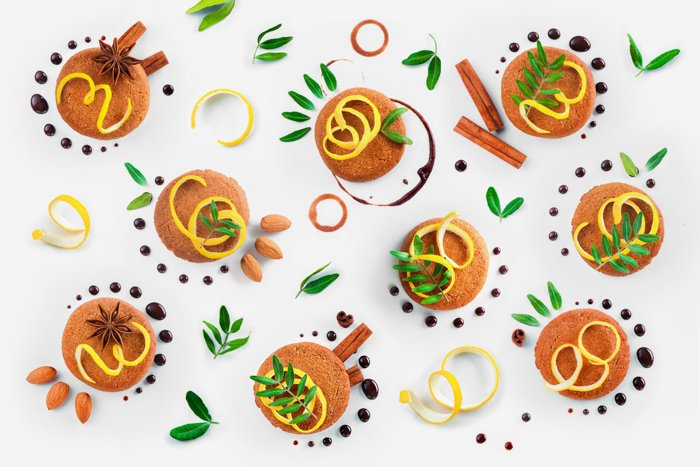 Overhead photo of cookies, nuts, leaves and chocolate on white background - still life photography ideas.