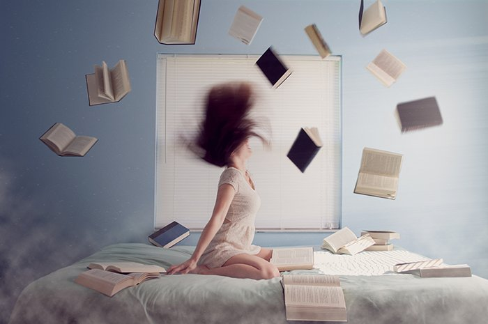 Laci Slezak surrealism photography of a girl sitting on a bed, books flying around.