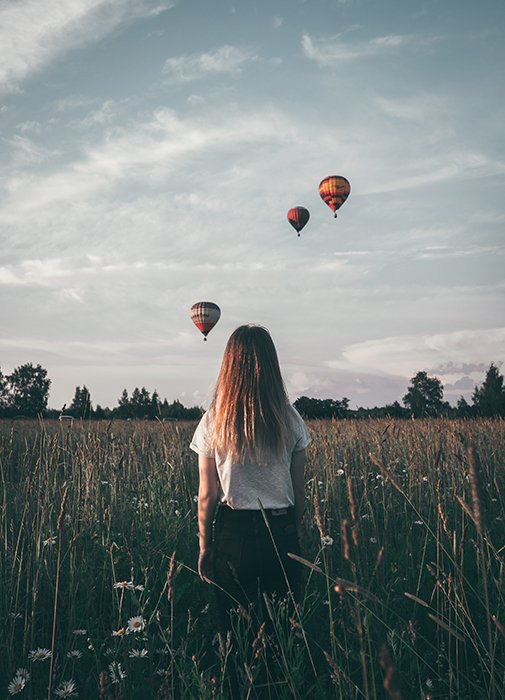 Natalya Letunova artistic photo of a girl standing in a field watching hot air balloons in the sky - surreal photography